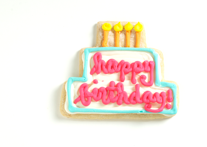 A Birthday Cake Shaped Cookie With Smooth Royal Icing